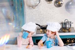 Cute little kids in chef hats drinking tea and eating cookies. In kitchen stock photo