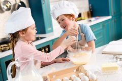 cute little kids in chef hats smiling each other while whisking dough royalty free stock photo
