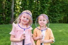 Cute little kids holding badminton rackets and smiling at camera. In park stock image
