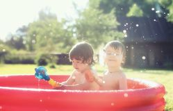 Baby splashing in the pool outdoors. Cute little kids on nature in summer on the site in a country house Royalty Free Stock Photo