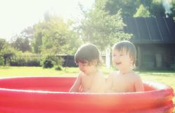 Baby splashing in the pool outdoors. Cute little kids on nature in summer on the site in a country house Stock Photos