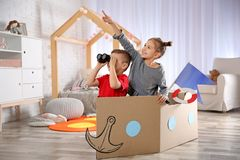 Cute little kids playing with binoculars and cardboard boat. In bedroom stock photos