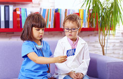Cute little kids playing doctors in office Stock Photos