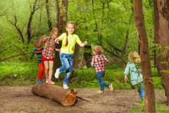 Cute little kids playing on a log in the forest. Portrait of cute little kids playing on a log, walking, jumping and balancing in the forest royalty free stock images