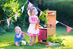 Cute little kids playing with toy kitchen in the garden. Funny curly little girl and adorable baby boy, cute brother and sister, playing together with a vintage Royalty Free Stock Photo