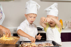 Cute Little Kids Putting Cheese on Pizza Royalty Free Stock Image