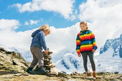 Children hiking in mountains. Cute little kids resting in Gornergrat glacier, Switzerland, Two young children playing together in mountains, small boy and his Royalty Free Stock Photos