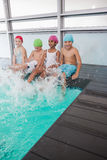 Cute little kids sitting poolside Royalty Free Stock Images