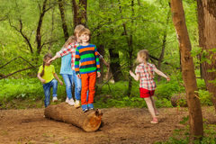 Cute little kids walking on log of tree in park royalty free stock photography