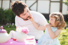 Cute little lady playing tea party with her caring father Royalty Free Stock Photo