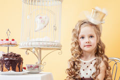 Cute little lady posing sitting at table Royalty Free Stock Photo
