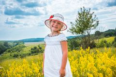 Cute little laughing girl walking in field of yellow flowers Royalty Free Stock Image