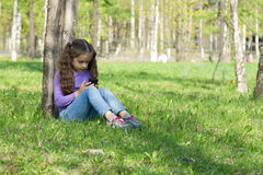 Cute little long-haired girl sitting on the grass in a park with a mobile phone in her hands and sending message on phone mobile Royalty Free Stock Photography