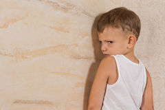 Cute Little Mad Boy Isolated on Light Brown Walls. Cute Little Mad Boy Wearing White Undershirt Isolated on Light Brown Walls Royalty Free Stock Photos