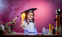Cute little magician holding fire in palm of hand Stock Photos