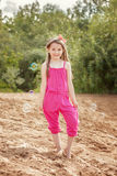 Cute little model posing in pink overall at beach Royalty Free Stock Photo