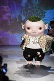Cute little monster Wuba and designer Vivienne Tam walks the runway. NEW YORK, NY - SEPTEMBER 10: Cute little monster Wuba and designer Vivienne Tam walks the royalty free stock photos