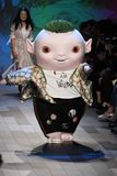 : Cute little monster Wuba and designer Vivienne Tam walks the runway. NEW YORK, NY - SEPTEMBER 10: Cute little monster Wuba and designer Vivienne Tam walks the stock photo