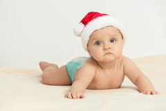 Cute little 5 months old baby boy wearing Santa Claus hat. Intimate Christmas Feeling - Cute little baby boy lie prone and wearing Santa Claus hat Stock Photo
