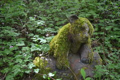 Cute little mossy bear cub. This is a wood carving of a bear cub. Over time it has grown moss so it looks like fur almost. It sits in a nice little clearing in Royalty Free Stock Photos