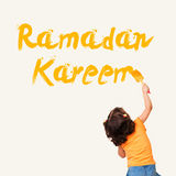 Cute little Muslim girl drawing Ramadan Kareem. With painting brush on wall background stock image