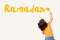Cute little Muslim girl drawing Ramadan. With painting brush on wall background Stock Photo