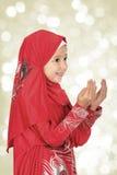 Cute Little Muslim Girl wearing hijab - making duaa  praying to. Allah Stock Photo