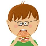 Cute little nerd boy with glasses eats burger Royalty Free Stock Images