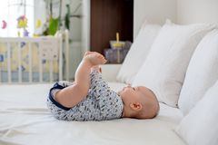 Cute little newborn baby boy, playing in bed in the morning. Baby activity Stock Photo