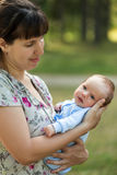 Cute little newborn baby child on mother hands walking outdoor Royalty Free Stock Photos