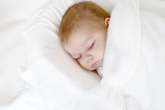 Cute little newborn baby girl sleeping wrapped in blanket Royalty Free Stock Images