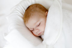 Cute little newborn baby girl sleeping wrapped in blanket Stock Images