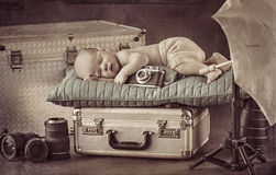 Cute little photographer sleeping on the suitcase Stock Image