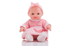Cute little plastic baby doll with blue eyes sitting isolated o