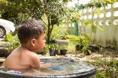 Cute little play water and take a bath in garden. Vintage Stock Image