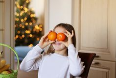 Cute little playful funny girl having fun holding orange tangerines in front of her eyes royalty free stock photo