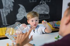 Cute little toddler boy at speechtherapist session. Cute little playfull toddler boy at speech therapy session. Private one on one homeschooling with didactic Stock Photos