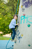 Cute little preschool boy, climbing on a rock wall with rope Stock Images