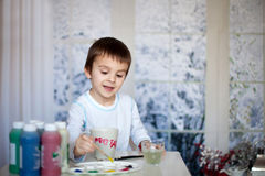 Cute little preschool boy, drawing picture on mug for his father Royalty Free Stock Images