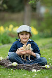 Cute little preschool child, boy, playing with easter eggs and c. Hicks in spring blooming garden, sitting in handmade nest, easter happiness childhood concept Royalty Free Stock Image