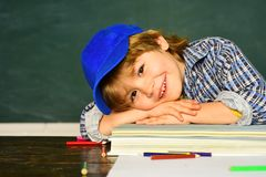 Cute little preschool kid boy in a classroom. Schoolchild. Happy mood smiling broadly in school. Schoolboy. Elementary. School and education. First school day royalty free stock image