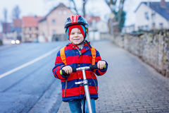 Cute little preschool kid boy riding on scooter riding to school. Stock Image