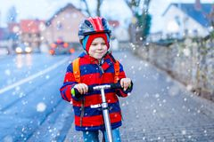Cute little preschool kid boy riding on scooter riding to school. children activities outdoor in winter, spring or. Autumn. funny happy child in colorful stock photo