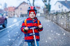 Cute little preschool kid boy riding on scooter riding to school. Children activities outdoor in winter, spring or autumn. funny happy child in colorful Stock Image