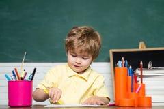 Cute little preschool kid boy study in a classroom. Cheerful smiling little boy Pupil having fun against blackboard royalty free stock photography