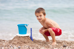 Cute little preschooler boy, playing in the sand on the beach wi Stock Image