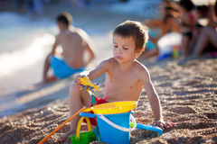 Cute little preschooler boy, playing in the sand on the beach wi Royalty Free Stock Photos