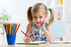 Cute little preschooler child drawing at home. Cute little girl child kid drawing at home royalty free stock image