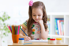 Cute little preschooler child drawing at home Stock Images
