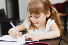 Cute little  preschooler girl is drawing with colorful felt-tip pens Stock Image